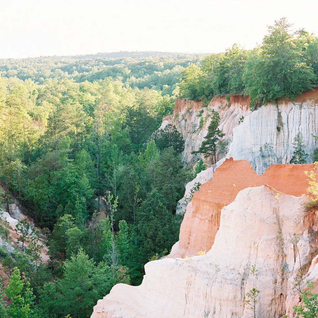A beautiful overlook of mountains covered in red clay with trees growing all around.  This is a scene right out of a national park.