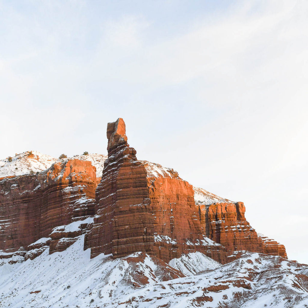 A beautiful outcropping of red rock covered in snow.  You might see this view at a national park.