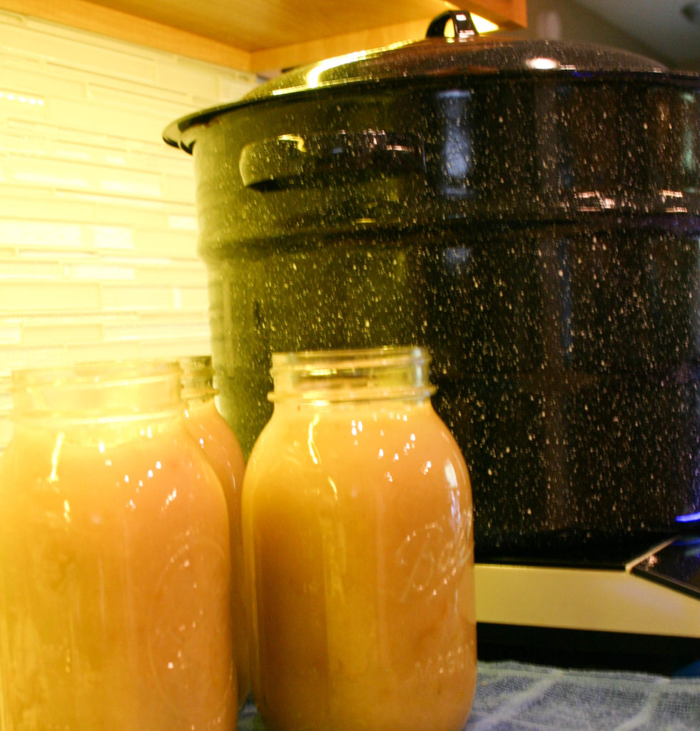 Mason jars filled with applesauce sitting next to a canning pot waiting to be sealed.