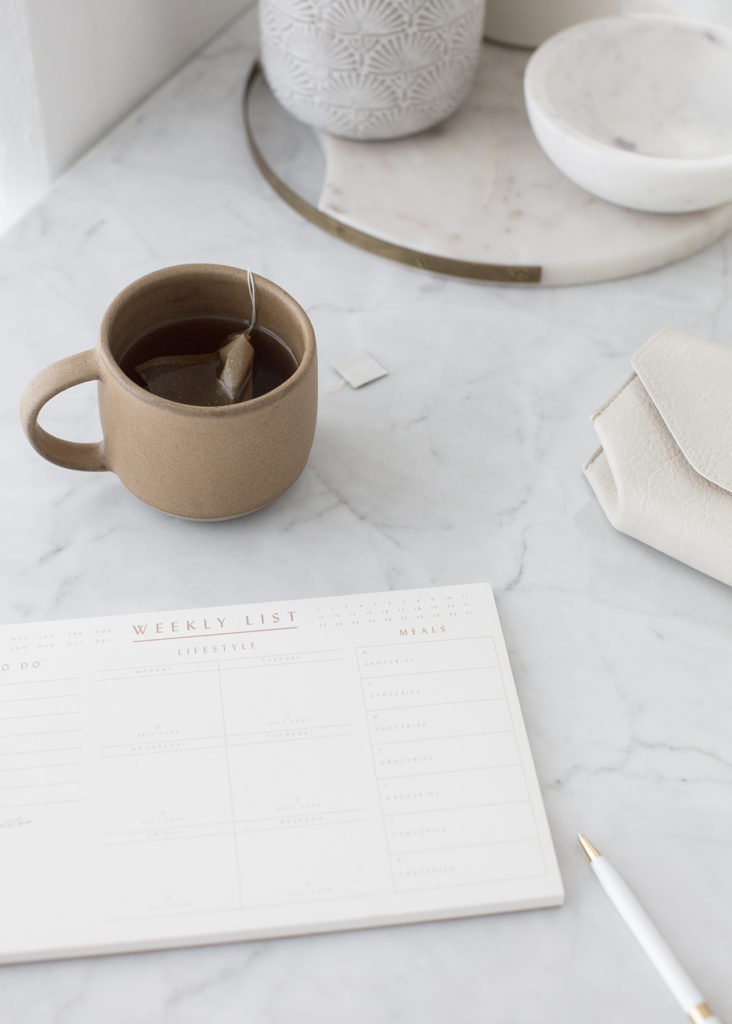 A cup of coffee sitting next to a to do list and a pen, to show that the most effective organizational tool can be a to do list.