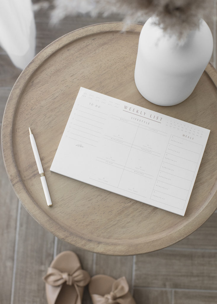 A weekly calendar sitting on a wooden table with a pen next to it.