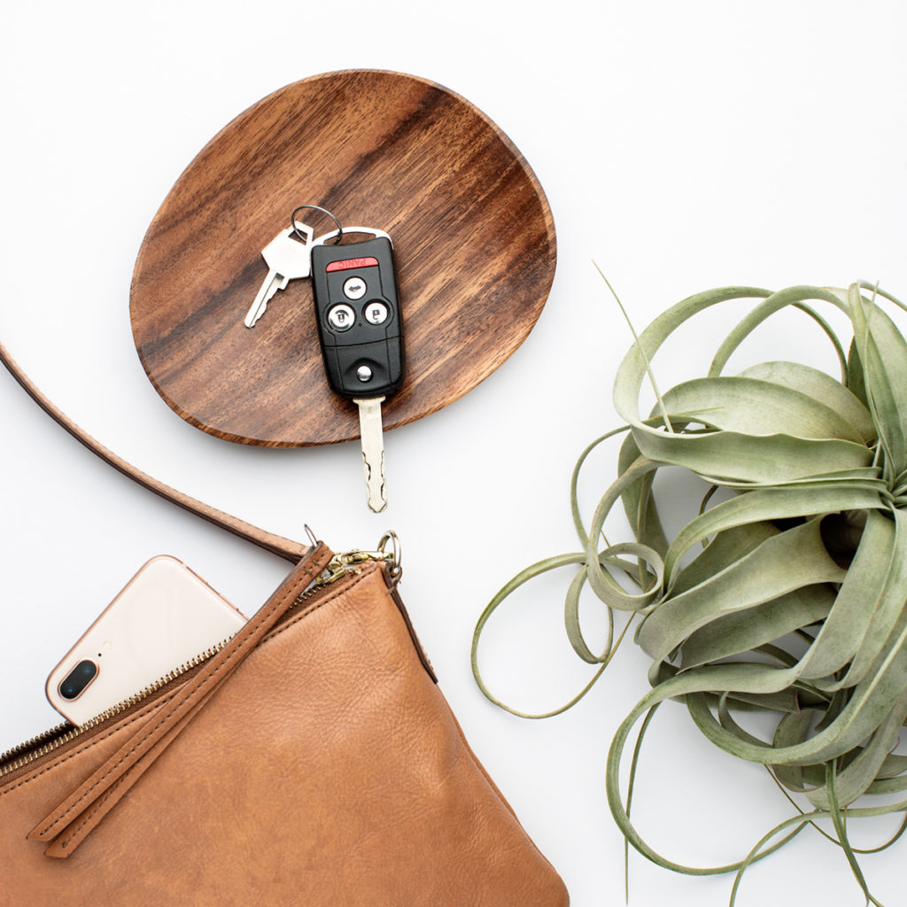 A set of car keys sitting in a small wooden dish next to a brown leather purse.