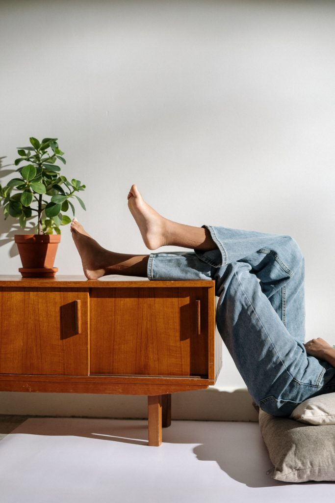 A lady resting on the floor with her blue jean legs propped up on a coffee table.
