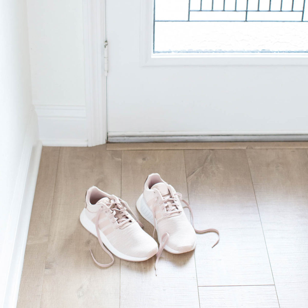 A pair of shoes sitting next to the door to remind you to organize your clothes by putting them away.
