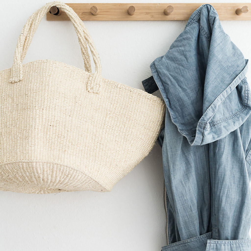A wicker bag and a jean jacket hanging on pegs to remind you to organize your clothes by putting them away.