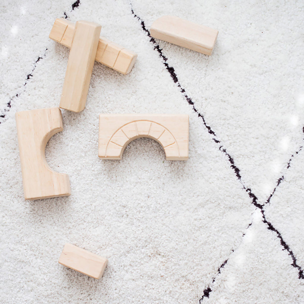 A set of children's wooden blocks laying on the carpet, waiting to be put away.