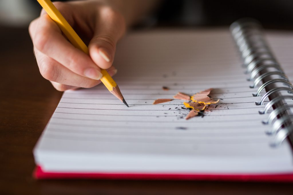 A child writing in a notebook with a pencil as part of their homeschooling work.