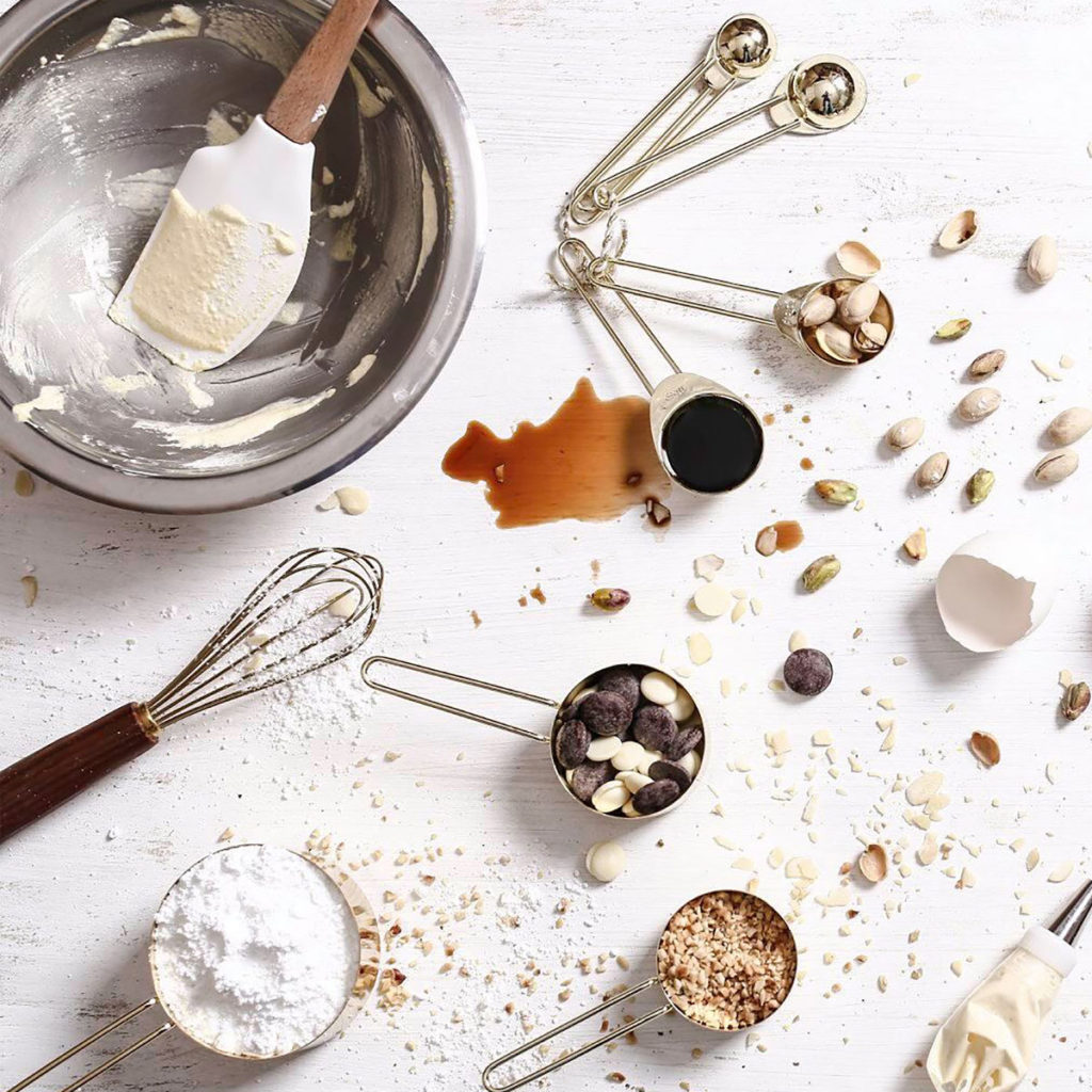 A counter covered in baking tools, flour, nuts, vanilla, and brown sugar.  Baking with children is messy!