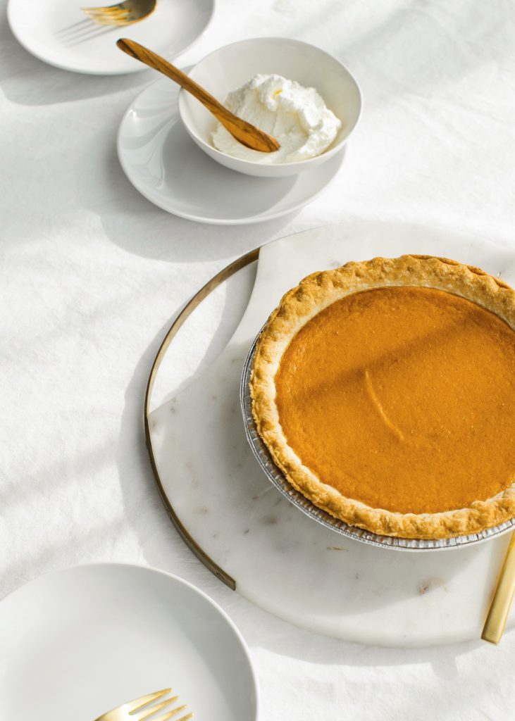 A pumpkin pie sitting next to a bowl of homemade whipped cream.  The perfect end to your holiday meal.