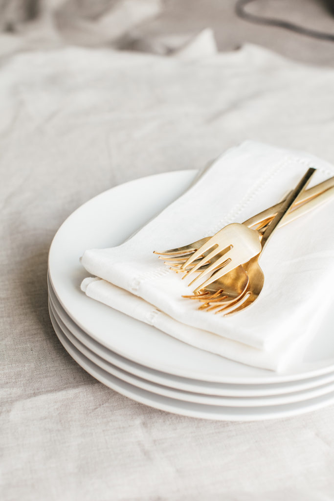 A stack of white plates with cloth napkins and forks sitting on top.  Setting the table for your holiday meal can be easy!