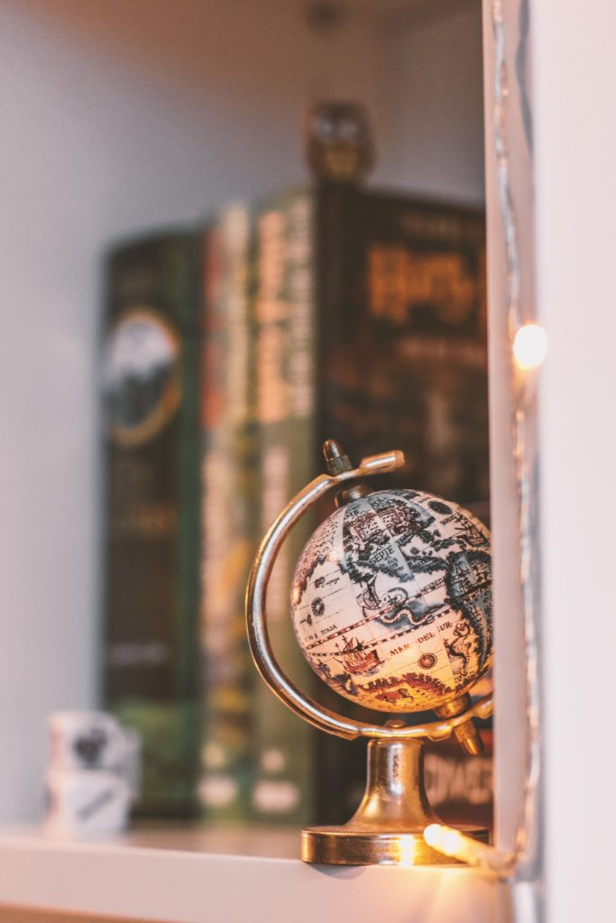 A small, vintage globe sitting on a shelf with older bound books reminding you of adventures around the world in years gone by.