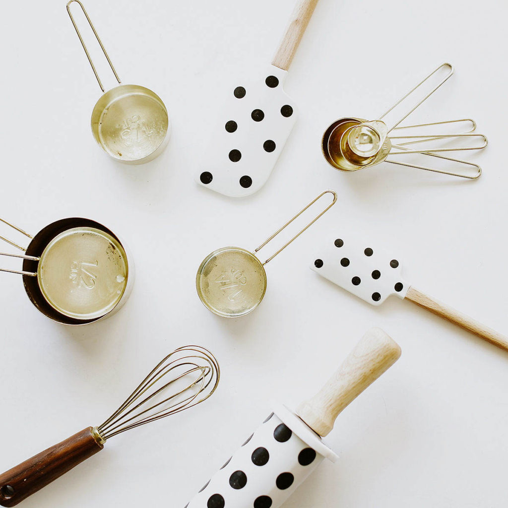 Polka dot kitchen utensils and gold colored measuring cups.