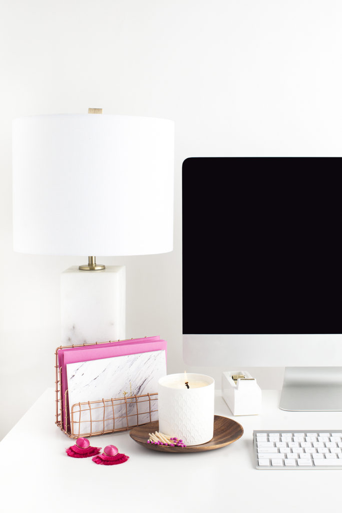 A neat and tidy desk top with a computer, lamp, and file holding system.