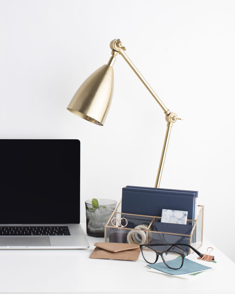 An organized desk with laptop, lamp, and file and office supply holder.