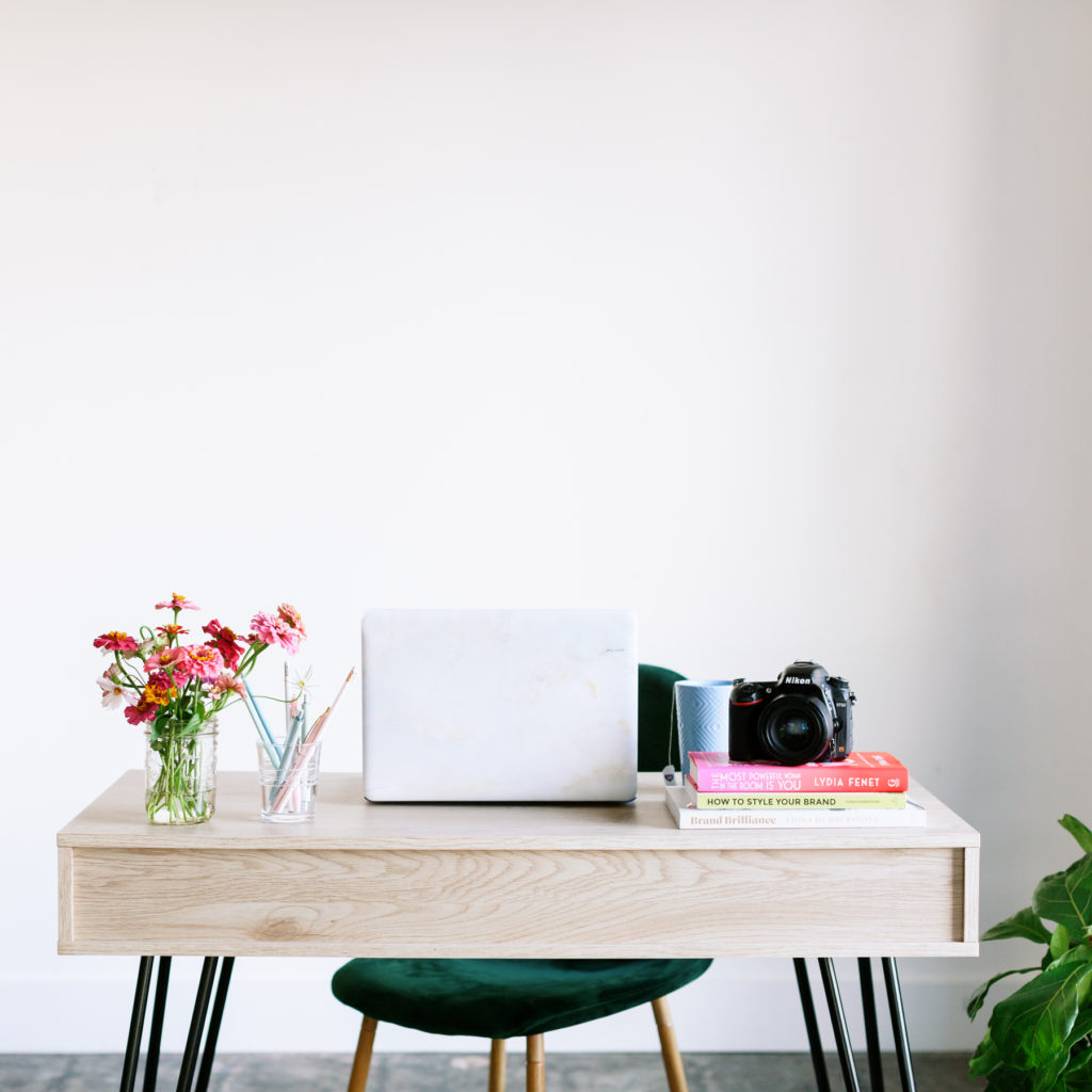 An organized and clear desk with a laptop and flowers on it.