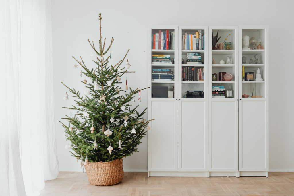 A Christmas tree standing next to a white bookshelf laden with books.