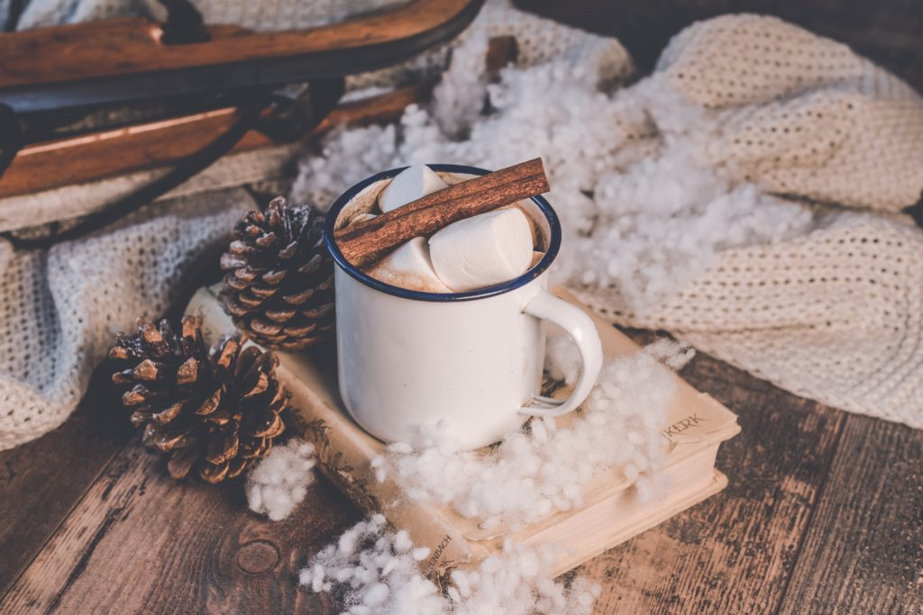 A hot cup of cocoa complete with marshmallows sitting on top of a chapter book.