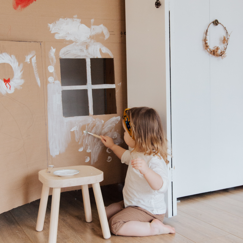 A little girl making a mess painting a cardboard playhouse.