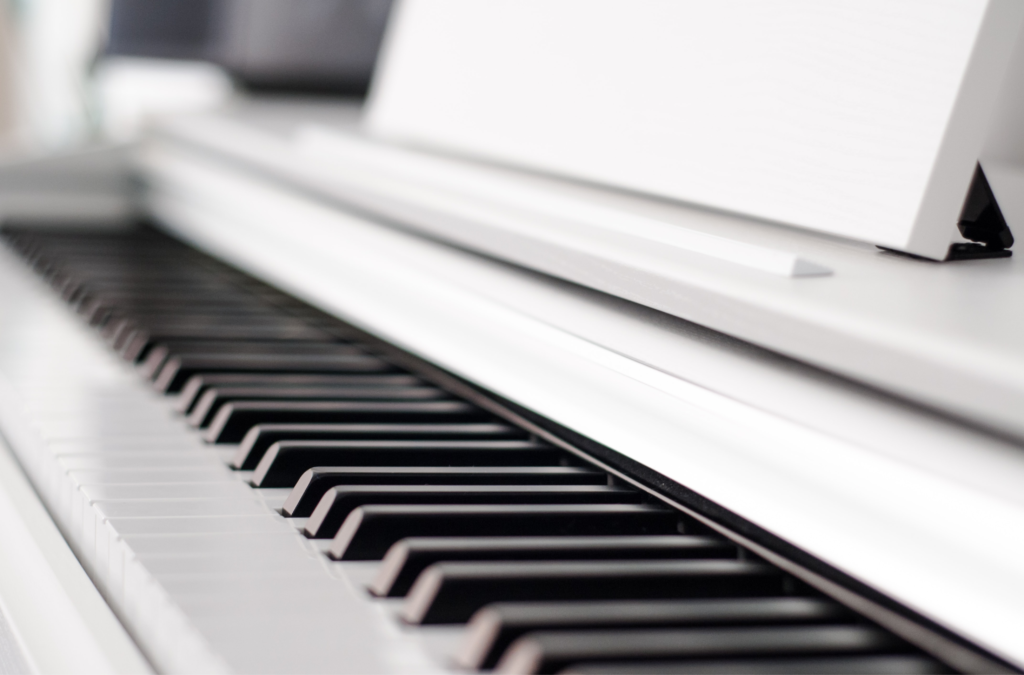 A white piano open to show the black and white keys.