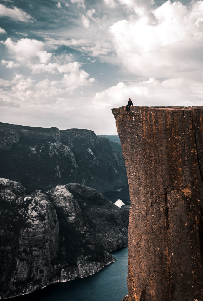 A mountain climber sitting on the top of a flat topped mountain looking out over the view with a sheer drop off underneath her.