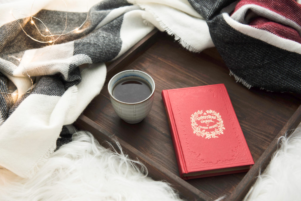 A red leather bound copy of 'A Christmas Carol' sitting next to a cup of coffee and some Christmas lights.