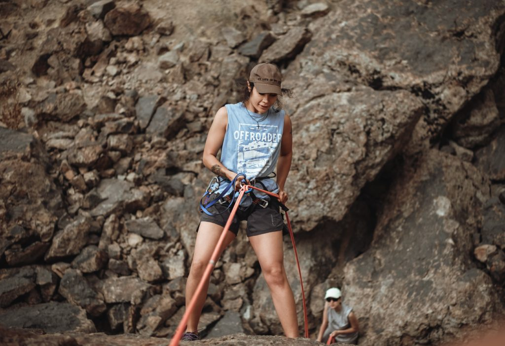 A mountain climber leaning back in her harness over a cliff as she begins to repel down the rock face.