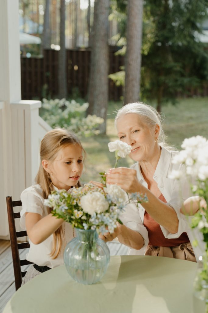 A grandmother teaching her granddaughter how to arrange flowers while telling her stories of her childhood.