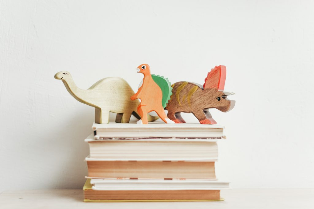 A stack of children's storybooks with wooden toy dinosaurs standing on top.