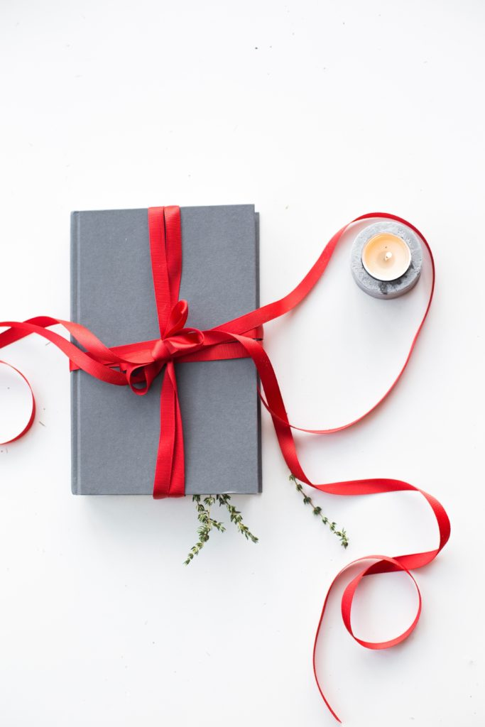 A hard bound book tied with a trailing red ribbon and sitting next to a candle.