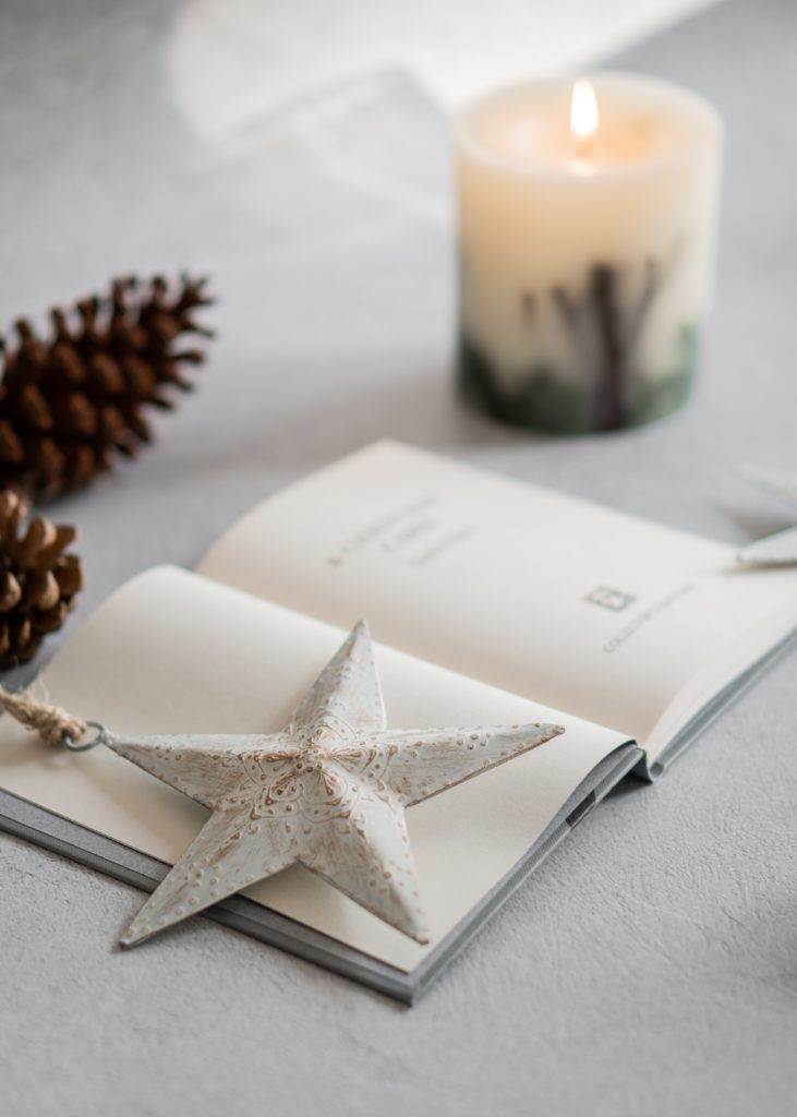 A copy of 'A Christmas Carol' held open by a star ornament, sitting next to some pinecones and a lit candle.