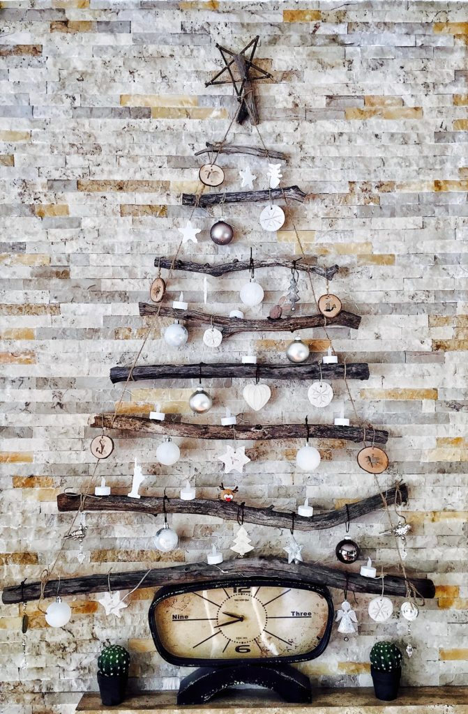 A Christmas tree fashioned out of wood and ornaments sitting on a squished clock.
