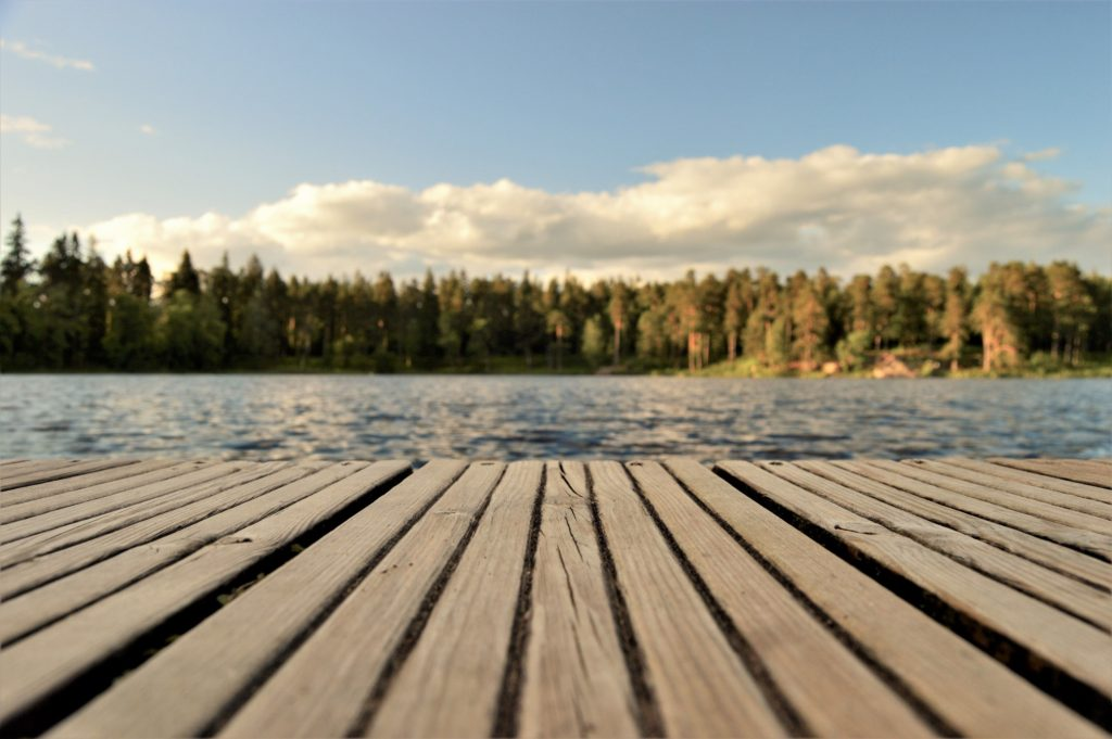 A beautiful photo skimming over a blue lake with a dock reminding us that beauty is found in imagination.