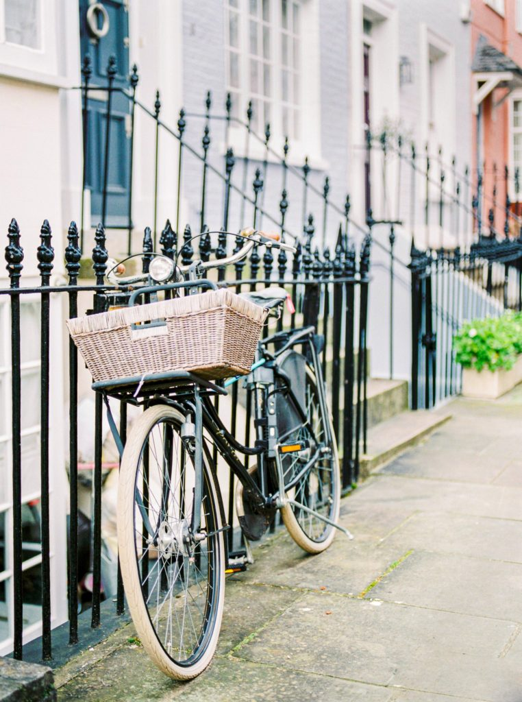A bicycle with a square basket on the front leaning against a black wrought iron fence.