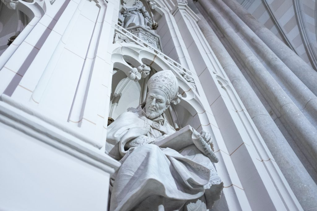 A statue of St Patrick carved into the side of a cathedral named in his honor.