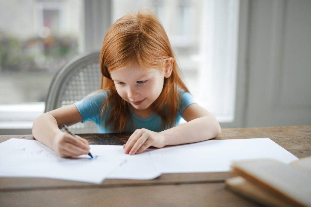 A red headed girl sitting at a table and working on her homeschool worksheets.