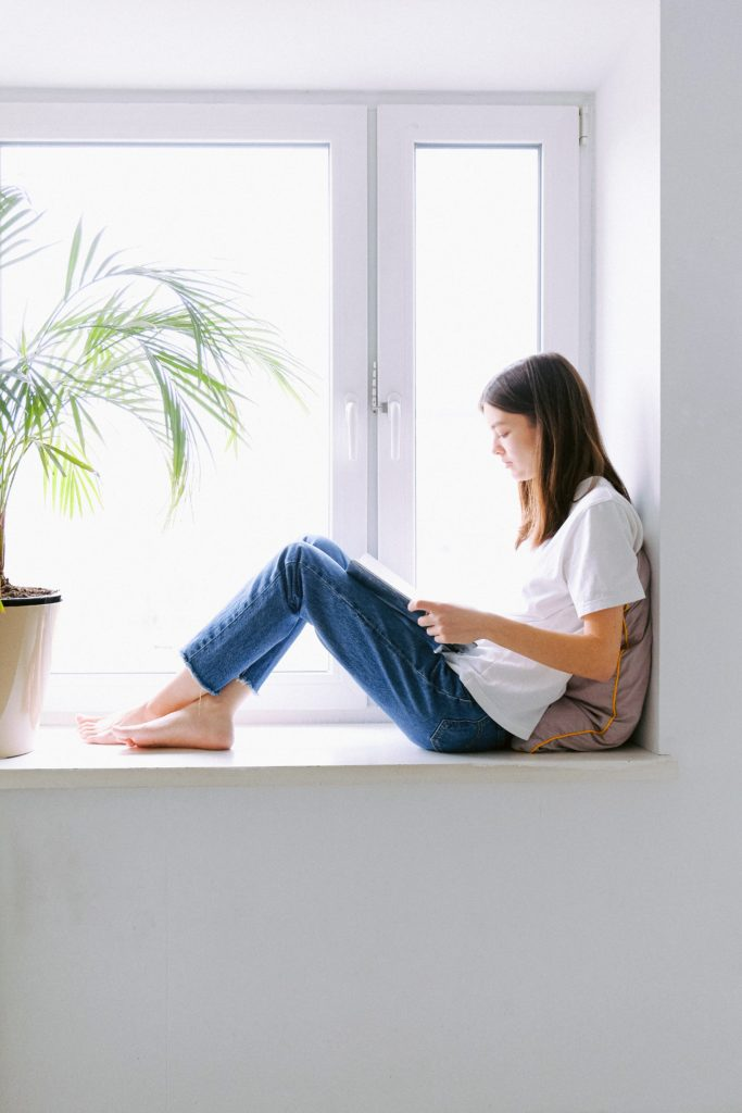 A young girl sitting in a window reading a book by the sunlight pouring through the window.