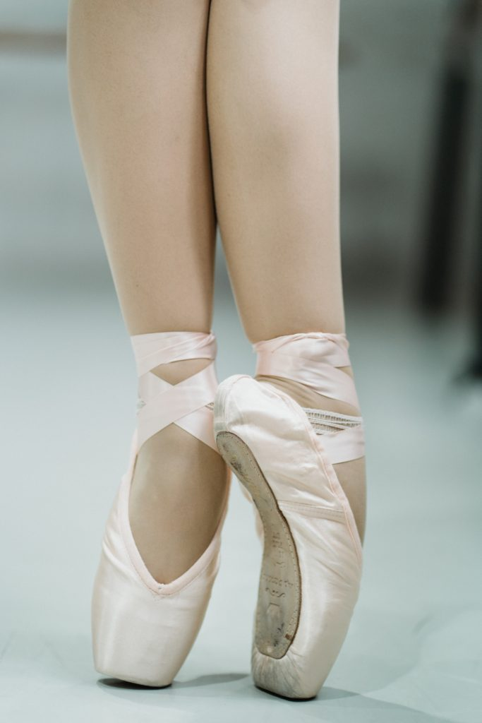 A ballerina's feet in pink ballet slippers standing en pointe.  Finding balance is essential to ballet.