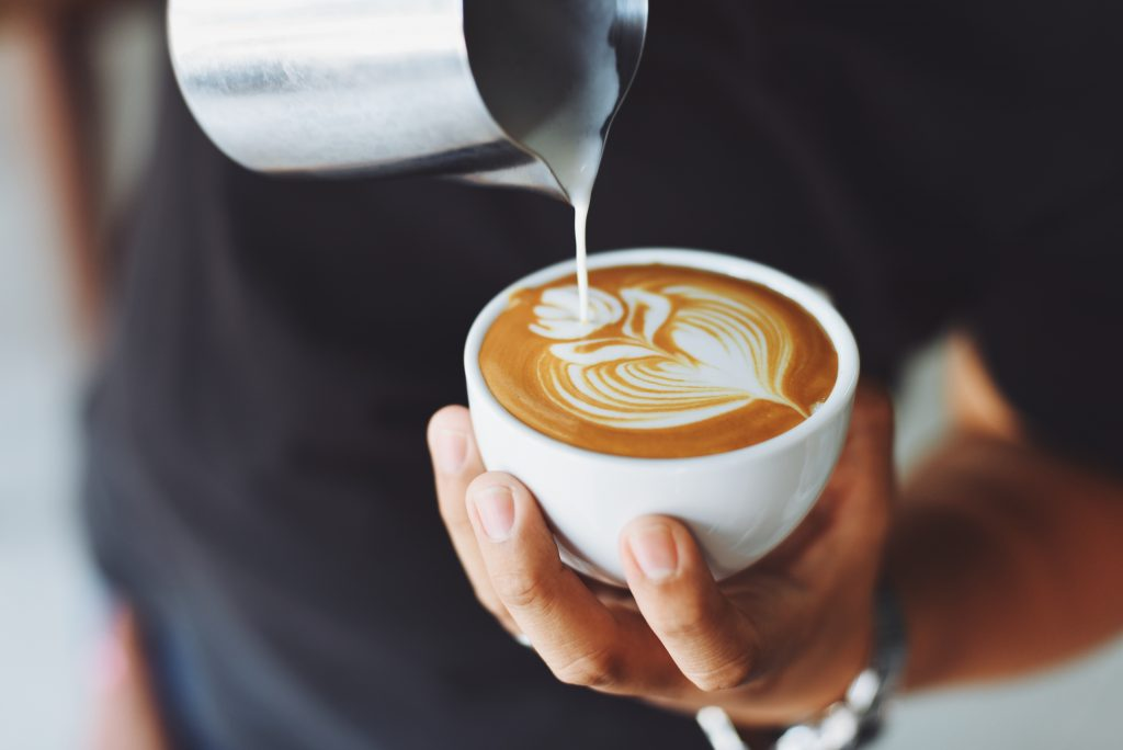 A barista pouring cream into a beautiful cup of coffee.