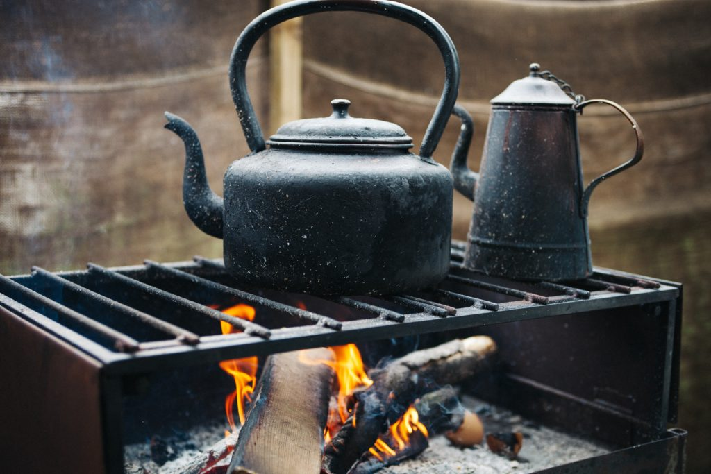 A cast iron pot and kettle sitting over an open fire perhaps like ones Laura Ingalls Wilder's family used on their trip west.