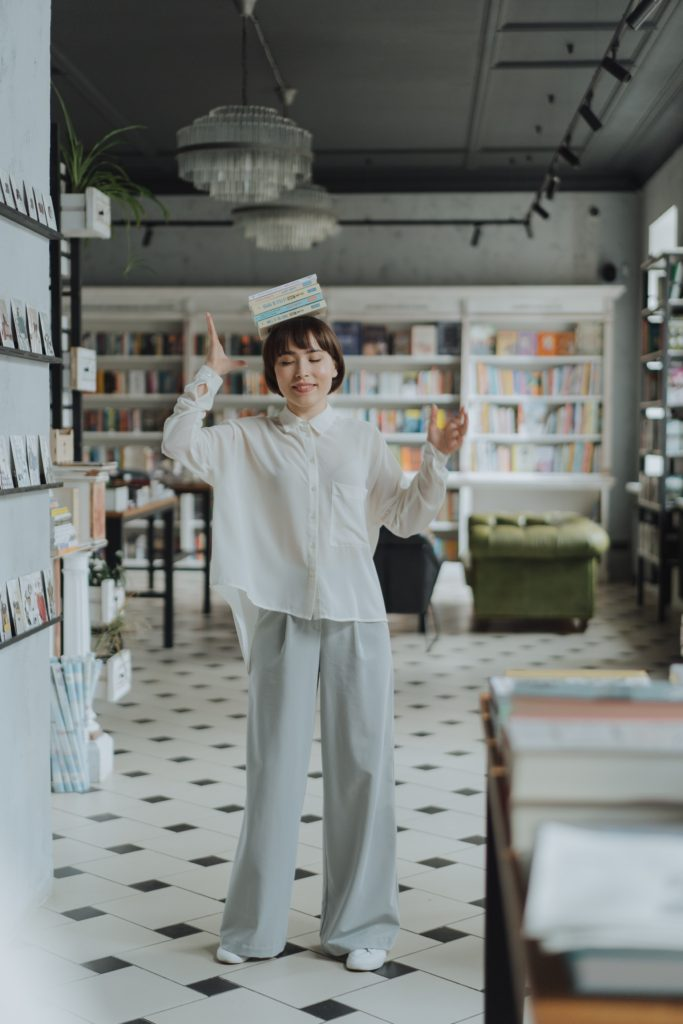 A person in a white shirt trying to balance a stack of books on her head and failing.