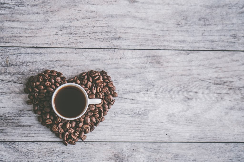 A cup of coffee sitting in a heart of coffee beans.