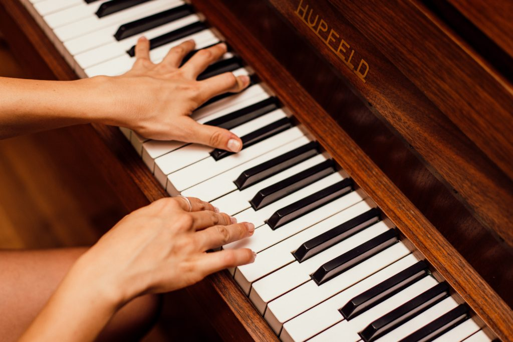 A close up of a person's hands playing the piano in harmony.