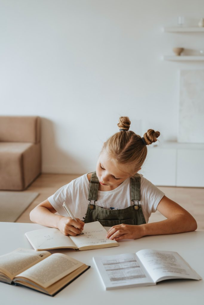 A young girl with pigtails writing in a notebook and doing her school work.