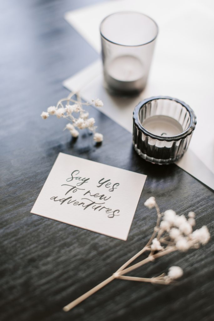 Two candles sitting on a wooden table next to some white flowers and a card that reads Say yes to new Adventures.