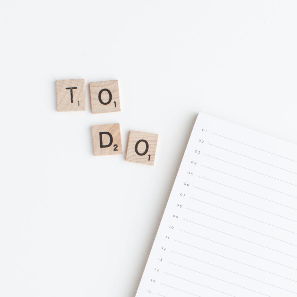 A to do list sitting next to scrabble letters spelling out To Do.