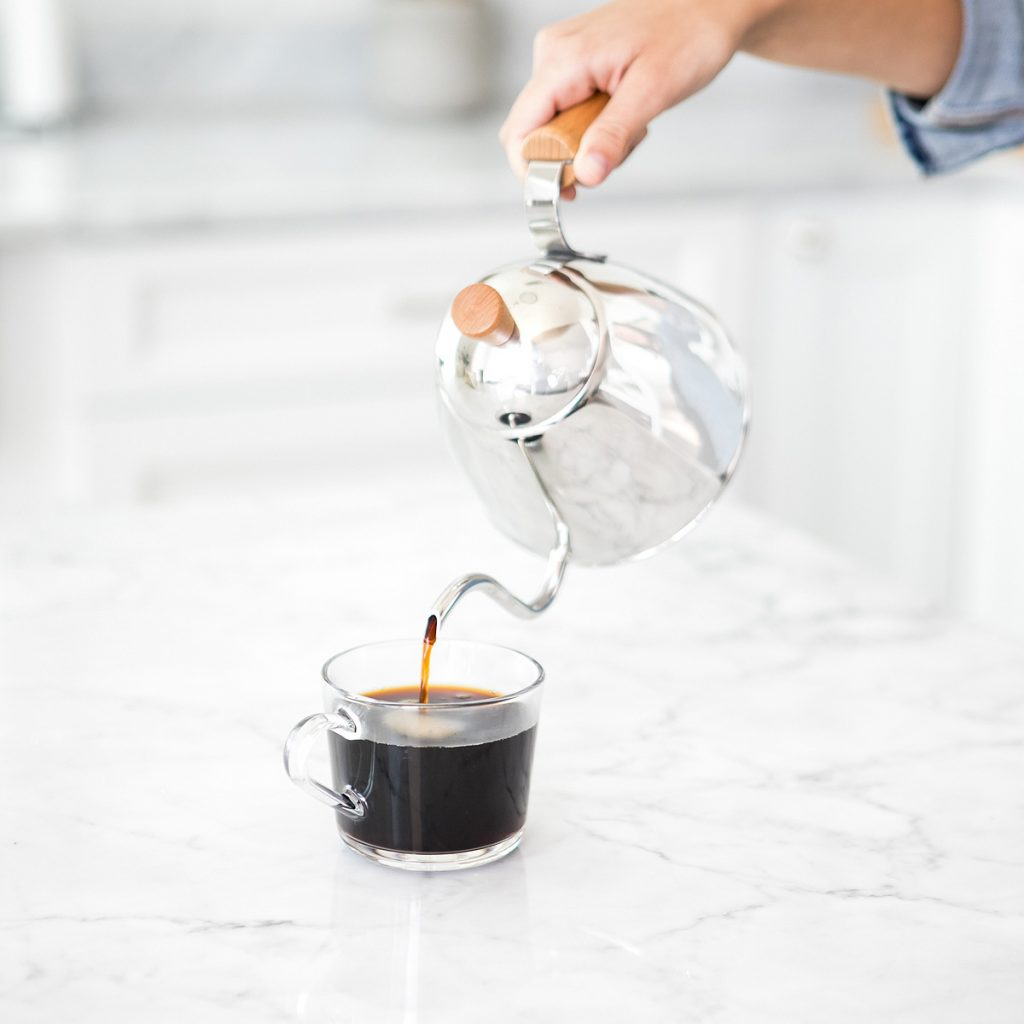 A hand pouring a cup of coffee from a silver coffeepot into a clear mug on a counter.