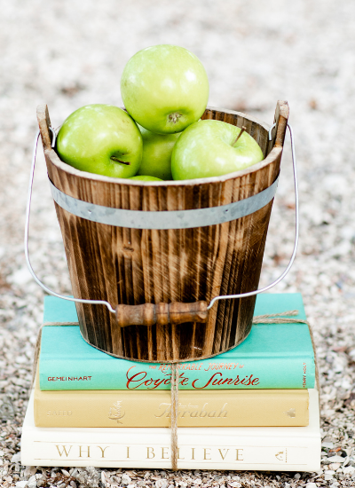 A wooden bucket of green apples sitting on top of 3 school books tied with twine.
