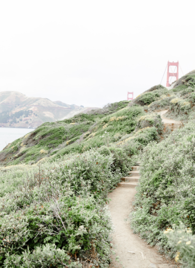 A dirt path leading through grass and bushes up the mountain with just a glimpse of the golden gate bridge on the other side
