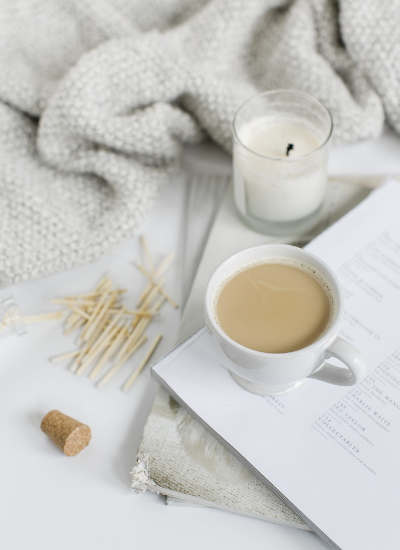 A cozy picture of a cup of coffee, a candle and some matches, a blanket, and a book showing that finding balance isn't the key. Finding harmony is.