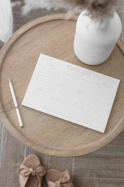 A weekly calendar sitting on a table with a pen and a vase of flowers showing that you have to plan for everyone in your family.